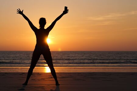 A young happy woman celebrating the end of lock down, on the beach at sunset after the coronavirus pandemic