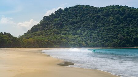 Turquoise sea water and gold fine sand surrender by a mountain with many green trees. Empty Sin Htauk Beach in Myanmar.