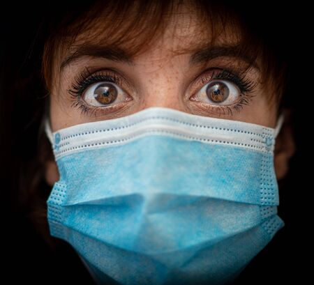 Close up of a scared young woman wearing a medical mask. The new normal worldwide life.