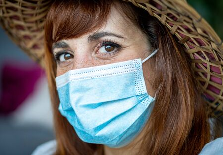A young woman wearing a medical mask and a hat at home. Concept of holiday after coronavirus pandemic