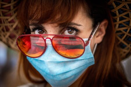 The new normal. A young woman wearing a surgical mask, red sunglasses and a hat ready for holidays after coronavirus lock down Imagens