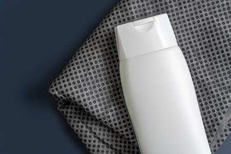 White Shampoo or gel bottle for cosmetic use on a grey Ionized Carbon Ultra-Absorbent towel