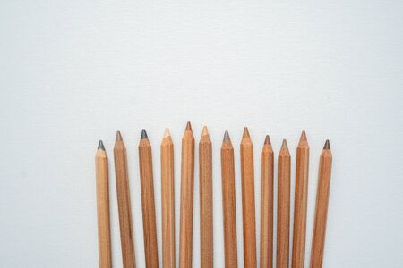 Diferents neutral color skin pencils disperse on a white canvas