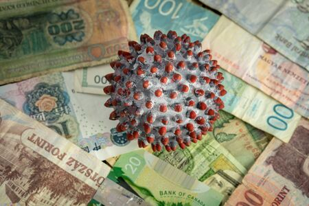 A ball painted like a SARS-CoV-2 virion on the middle of many banknotes from different countries Imagens