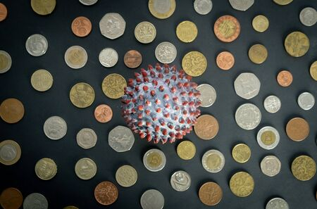 Top view of a ball painted like a SARS-CoV-2 virion on the middle of many coins from different countries