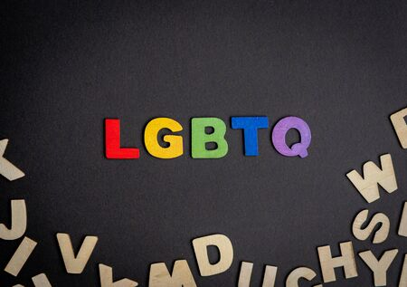 Colorful wooden letter forming the word LGBTQ and other wooden letters Imagens