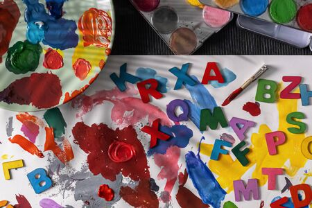 A messy table with different types of paints. Watercolor, oils paints working on colorful letters Imagens
