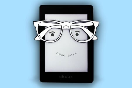 A black e-book with paper glasses and a happy face where it is written