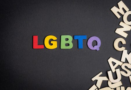 Colorful wooden letter forming the word LGBTQ and other wooden letters on the right side Imagens
