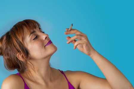 Worry less young woman smoking a rolling cigarette in relaxed pose Imagens