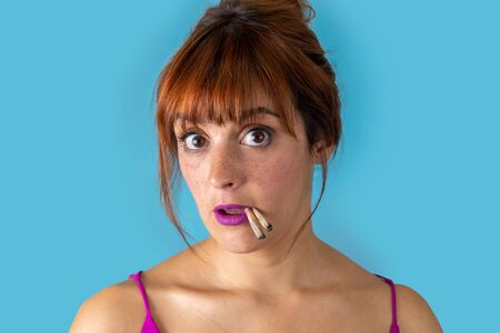 Young woman with red hair smoking two cigarettes at the same time on blue background
