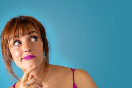 Young woman in reflective pose with copy space on blue background Imagens