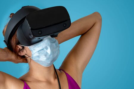 Young woman with virtual reality glasses and medical mask. Future vacation concept.