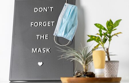 COVID-19 sign remembers to wear and at business stores. Message to the family to do not forget to take the medical mask to go outside during the coronavirus pandemic Stock fotó - 149833619