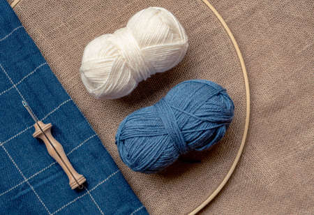Composition in diagonal with copy space of two wool balls and a wooden punch needle tool on a burlap fabric and a blue blanket