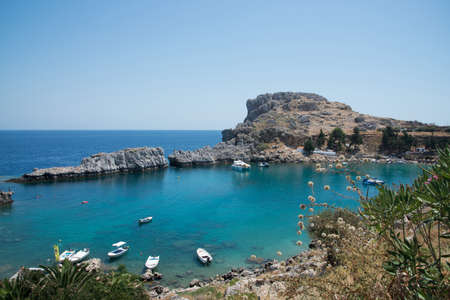 Beautiful bay close to Lindos, Rhodes, Greece. Many boats, blue water on a sunny day