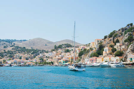 Yatch arriving at Symi harbor. View of the colorful village on a summer day. Dodecanese, Greece