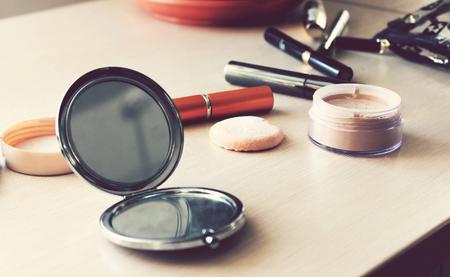 vistiendose: Espejo, polvo, soplo, rímel, delineador de ojos y otros cosméticos en la mesa Foto de archivo