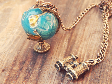 Necklace in the form of Earth globe and binoculars on a wooden background photo