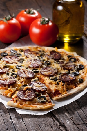 Homemade pizza with salami, cheese and black olives. photo