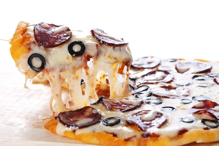Slice of pizza with salami, black olives and melted cheese.