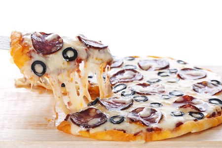 Slice of pizza with salami, black olives and melted cheese. photo