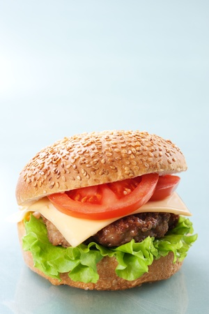 Cheeseburger with tomatoes and lettuce on grey background