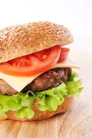 Cheeseburger with tomatoes and lettuce on a wooden table