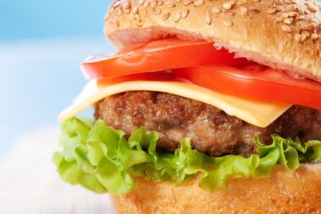 Cheeseburger con tomate y lechuga en una mesa de madera con fondo azul Foto de archivo