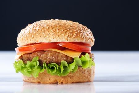 hamburguesa: Cheeseburger con tomate y lechuga sobre fondo negro