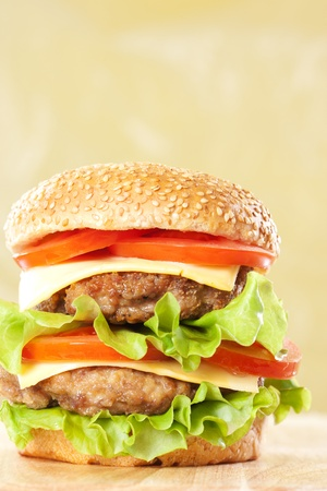 Double cheeseburger with tomatoes and lettuce on yellow background