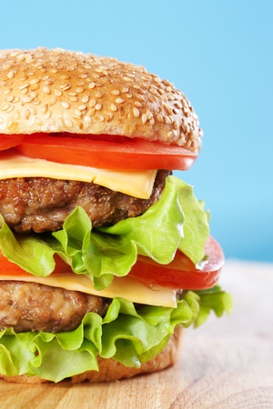 sesame seed bun: Double cheeseburger with tomatoes and lettuce on blue background