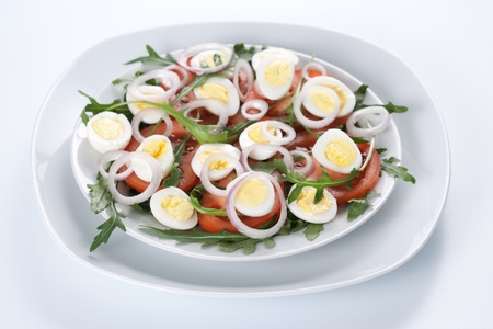 Healthy salad with tomatoes, onions, eggs and rucola photo