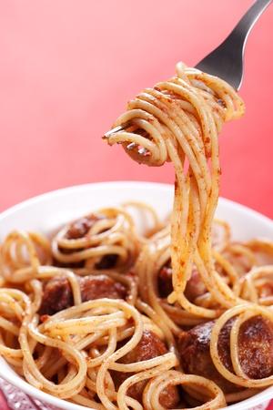 fork glasses: Pasta con polpette di carne e sugo di pomodoro su sfondo rosso  Archivio Fotografico