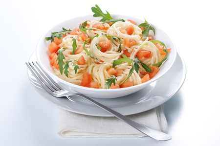 Pasta with tomato and rucola in bowl photo