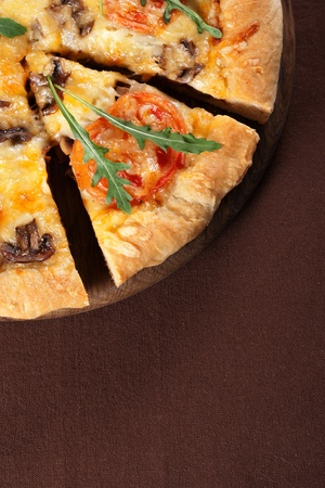 Fresh baked pizza with mushroom, tomatoes and rucola photo
