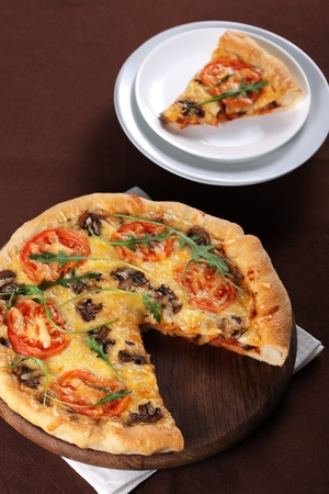 Fresh baked pizza with mushroom, tomatoes and rucola Stock Photo - 9231330