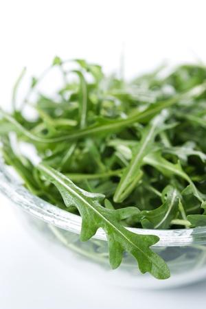Green rucola fresh salad in glass bowl  photo
