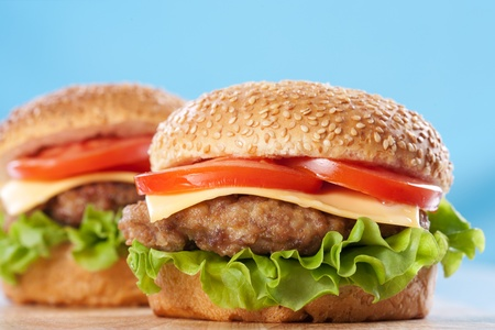 cheeseburgers: Two cheeseburgers with tomatoes and lettuce on a wooden table with blue background Stock Photo