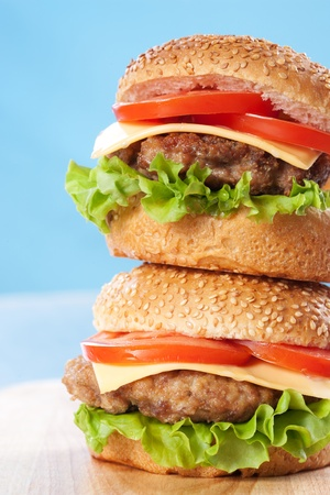 Two cheeseburgers with tomatoes and lettuce on a wooden table with blue background Stock Photo