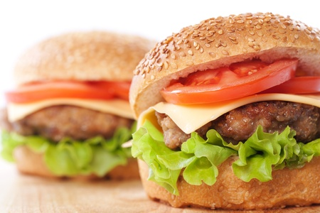 beef burger: Two cheeseburgers with tomatoes and lettuce on a wooden table