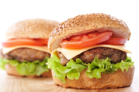 cheese burgers: Two cheeseburgers with tomatoes and lettuce on a wooden table