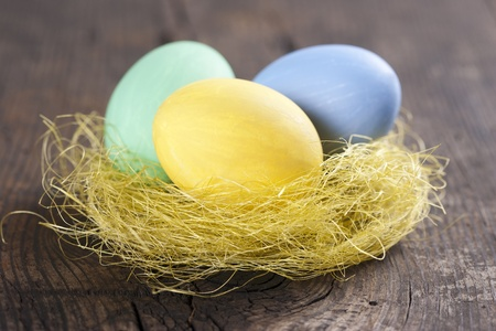 Colorful easter eggs in nest on wooden background  photo