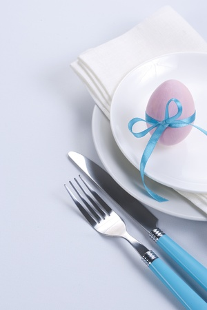 Easter table setting with plates, napkin, silverware and easter egg photo