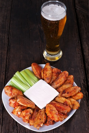 chicken fingers: Buffalo chicken wings on plate with blue cheese sauce and celery.