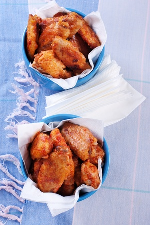 Buffalo chicken wings in bowls on blue tablecloth. Stock Photo