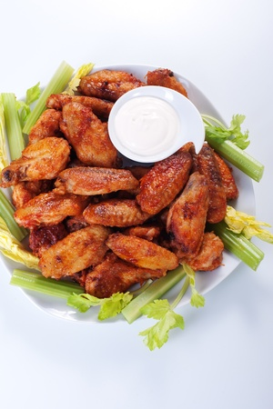 Buffalo chicken wings on plate with blue cheese sauce and celery. photo