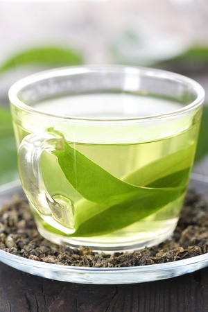 Cup of green tea on a wooden table photo