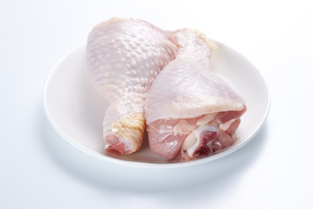 Two raw chicken legs on a plate on a white background photo