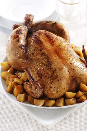 Tasty crispy roast chicken and potato on white plate.  Stock Photo